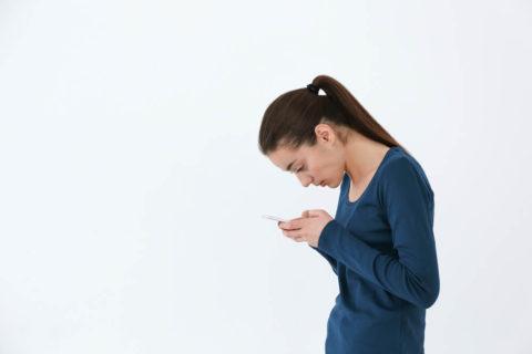 スマホをする女性、姿勢が悪い画像
